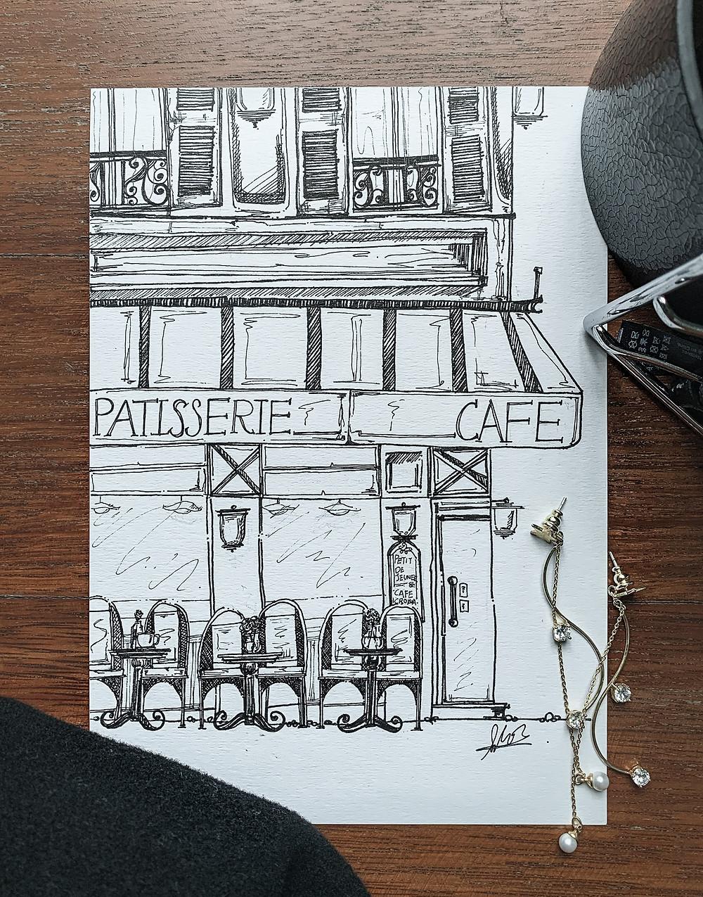 Flatlay of an ink illustration of a Parisian cafe, Joli Moon drop earrings, AllSaints wide black belt