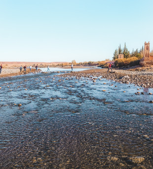 Tourists crossing the Ounila River to the Ait-Ben-Haddou entrance | RollingBear Travels.