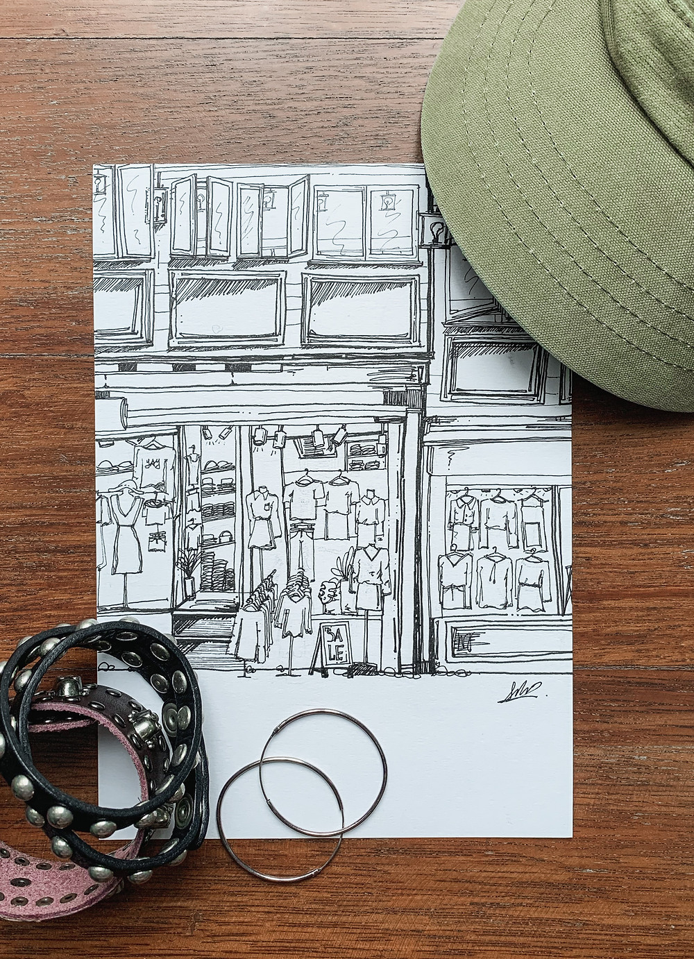 Flatlay of ink illustration of Seoul's clothes shopping streets, olive cap, leather bracelets