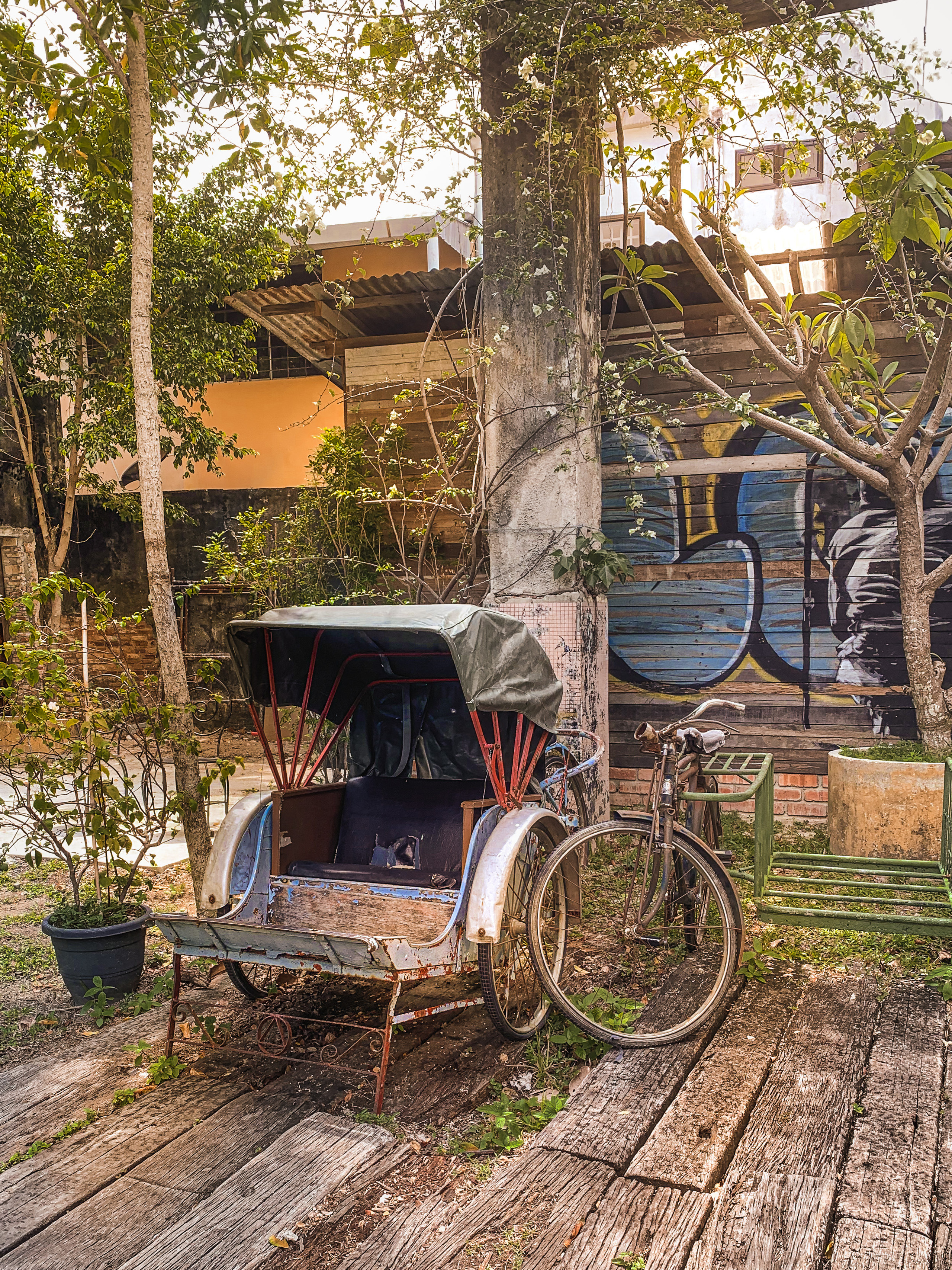 Antique trishaw and bicycle on timber planks against graffiti background, RollingBear Travels blog.