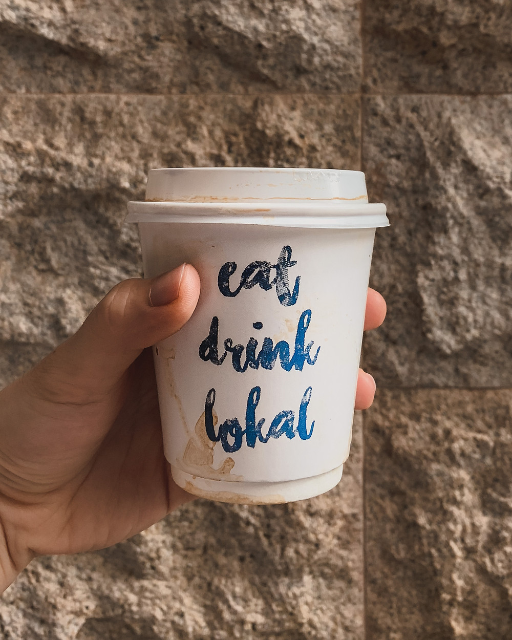 Rollingbear Travels blog/ hand holding paper coffee cup that says 'eat drink Lokal' against stone wall from The Lokal Cafe Singapore