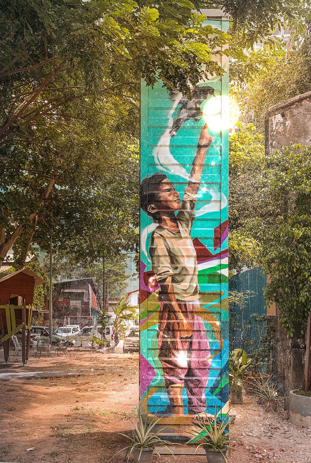 Colourful painted boy mural on perforated pillar of Hin Bus Depot, RollingBear Travels blog.