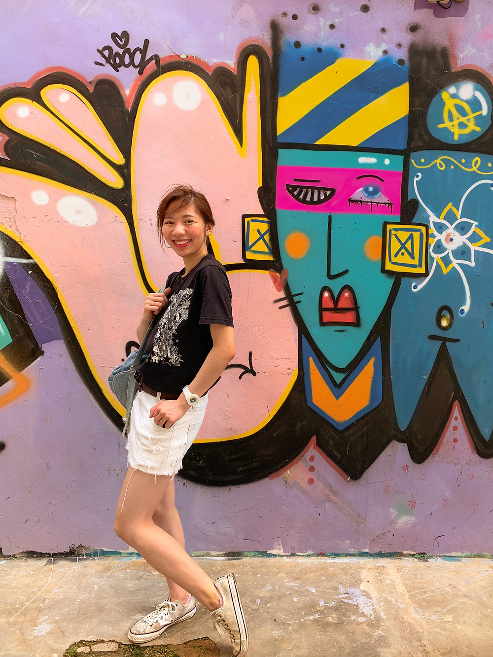 Black t-shirt, white ripped denim skirt, silver Converse sneakers, casual summer outfit by RollingBear Travels.