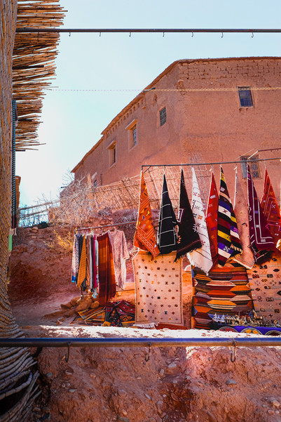 Makeshift Moroccan handicraft stall against Ait-Ben-Haddou's adobe buildings | RollingBear Travels.