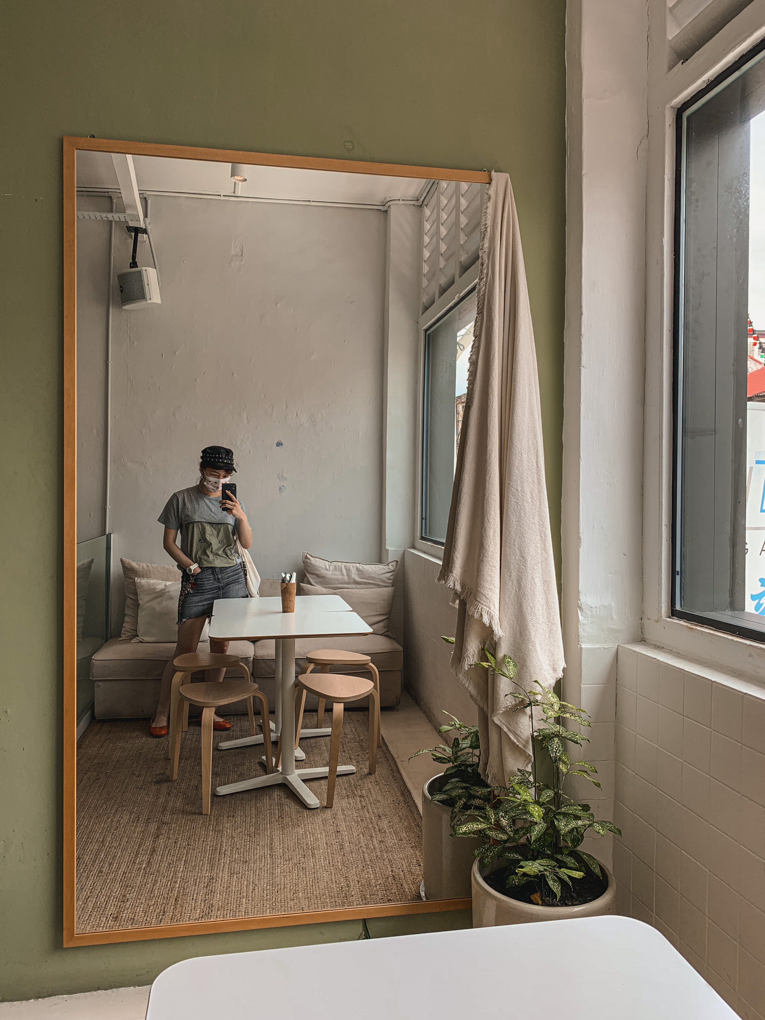 Travel blogger in cosy Muji-style interiors of Island Problems, Penang | RollingBear Travels.