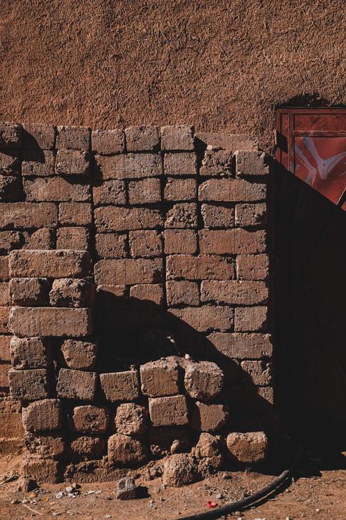 Ouarzazate travel experience: Mud bricks piled against adobe wall | RollingBear Travels.