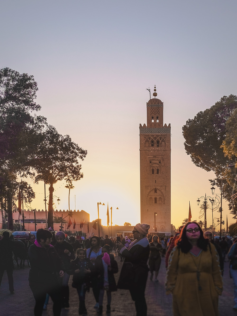 Silhouettes of the Koutoubia Mosque minaret and the crowds against the evening sky. | RollingBear Travels
