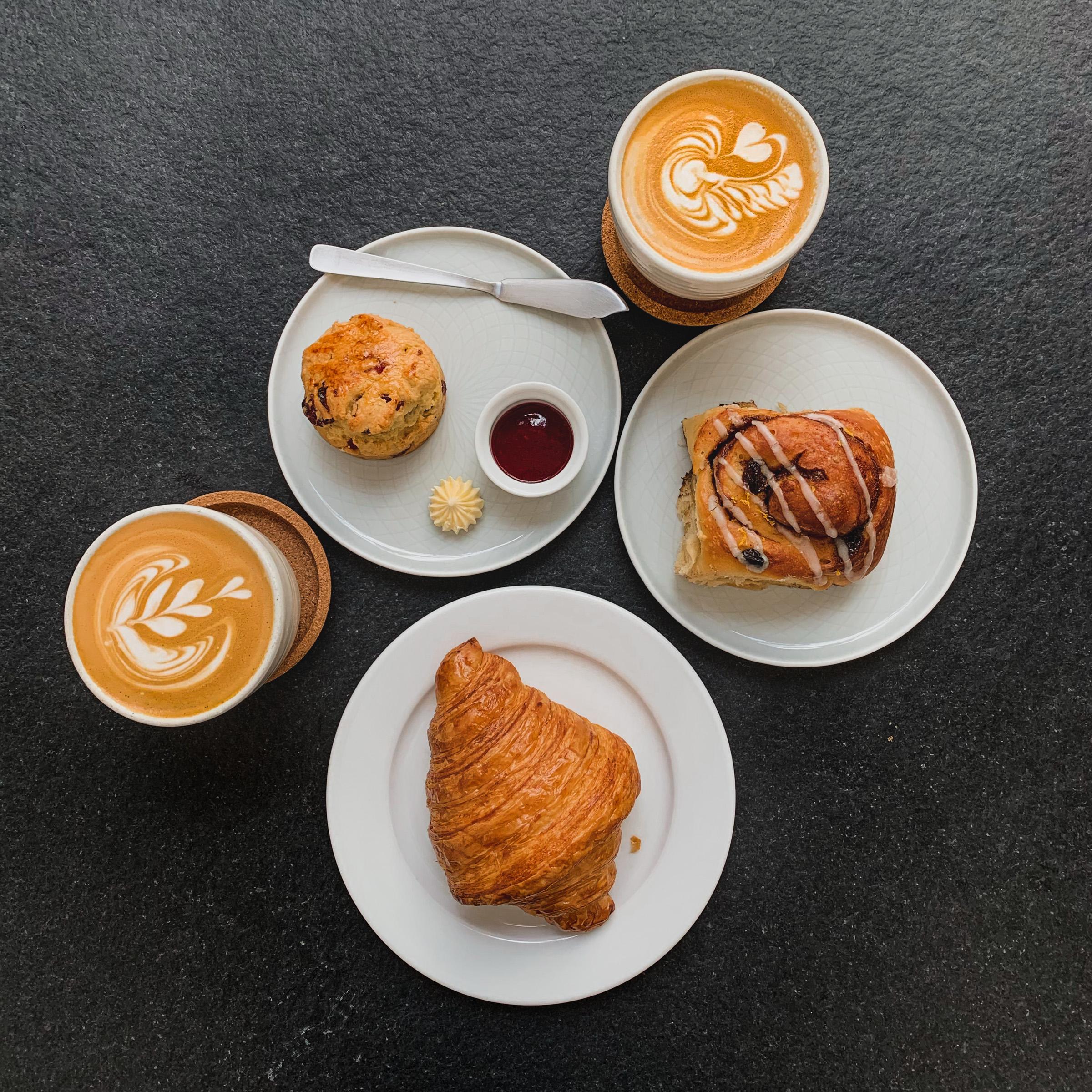 Lifestyle photography : Croissant, scone, cinnamon roll, latte spread, RollingBear Travels blog.