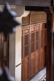 Heritage Peranakan timber screen doors of the Seven Terraces interior walkway, hotel photography by RollingBear Travels.