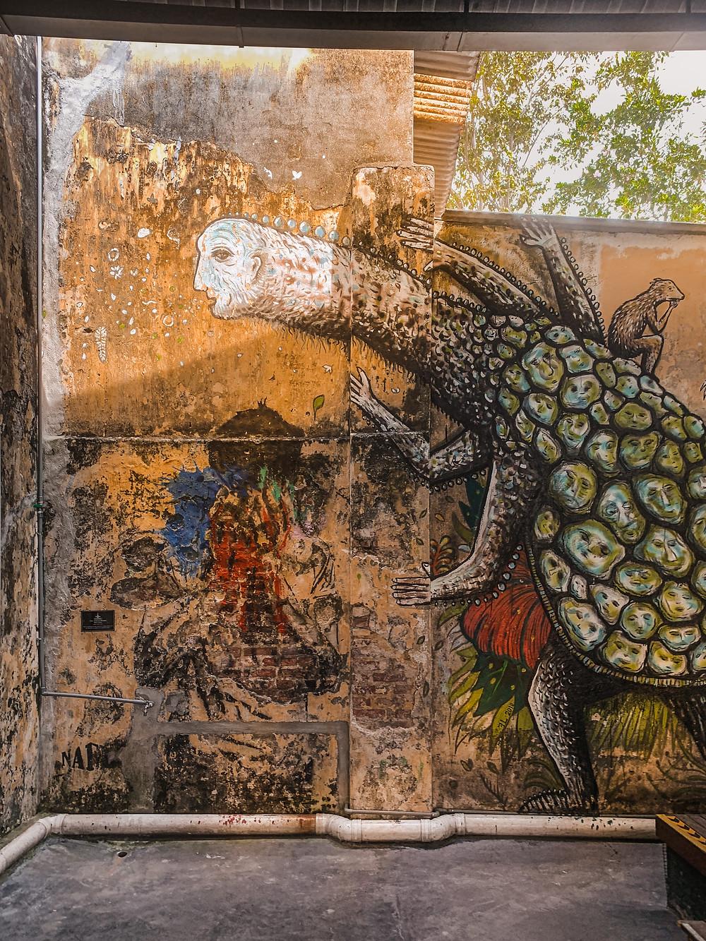 Fantasy art mural against orange wall of Hin Bus Depot, Penang, RollingBear Travels blog.