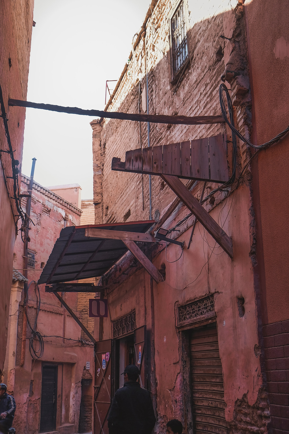 Street Photography: Claustrophobic lanes of pink adobe buildings with timber doors and crisscrossing wires of the Marrakech Medina. | RollingBear Travels
