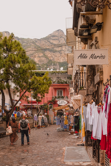 Clothes stalls and pastel buildings along a cobbled street in Positano. | RollingBear Travels.