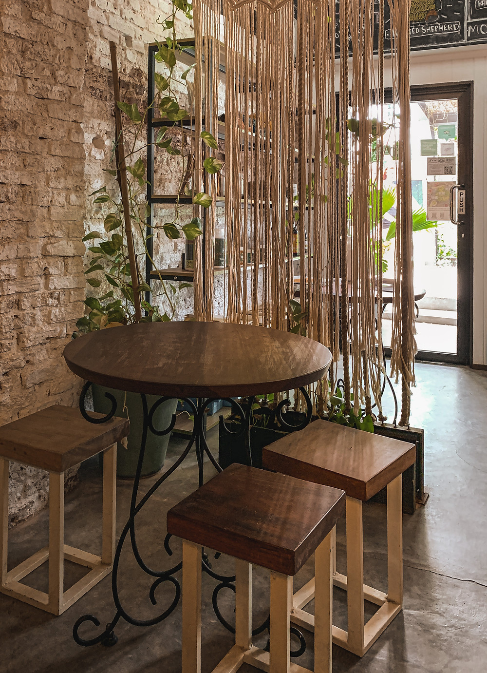 Wooden stool and table by a brick wall and rope partition corner of Wholey Wonder, Penang, RollingBear Travels blog.