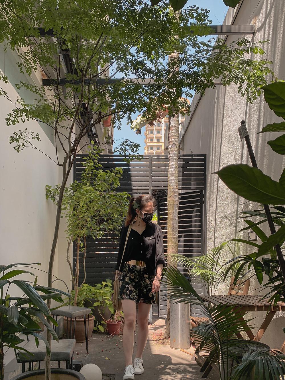 Style blogger in black shirt, gold metal belt, black floral skirt, white sneakers / RollingBear Travels.