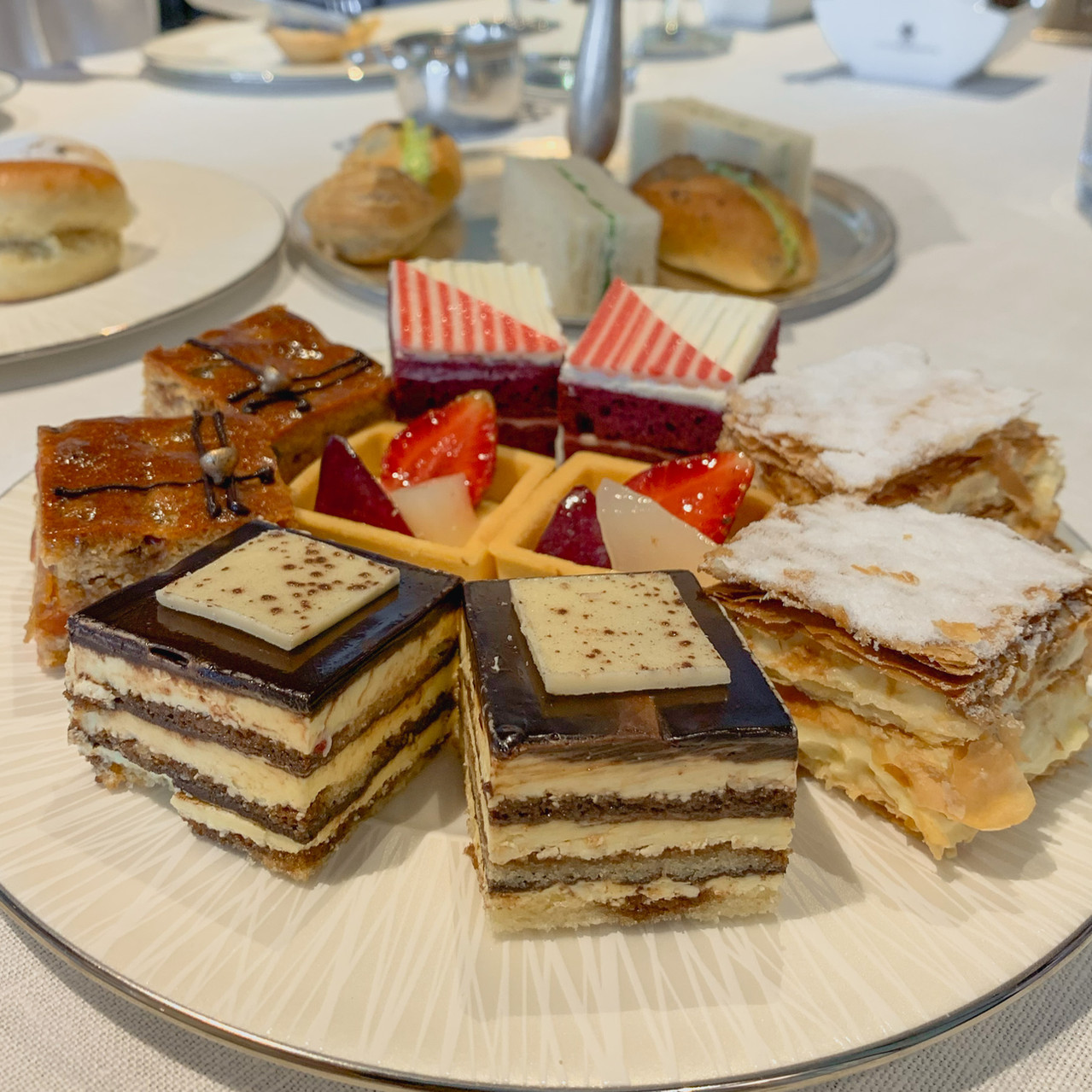 E&O Hotel afternoon tea: Mini cakes and fruit tarts on a white plate, RollingBear Travels blog.