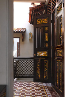 Gold gilded Peranakan timber comb doors of the Seven Terraces heritage hotel rooms / RollingBear Travels.