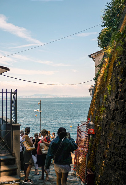 Female tourist walks down cliffside path towards the sea | Sorrento travel photography by RollingBear Travels.