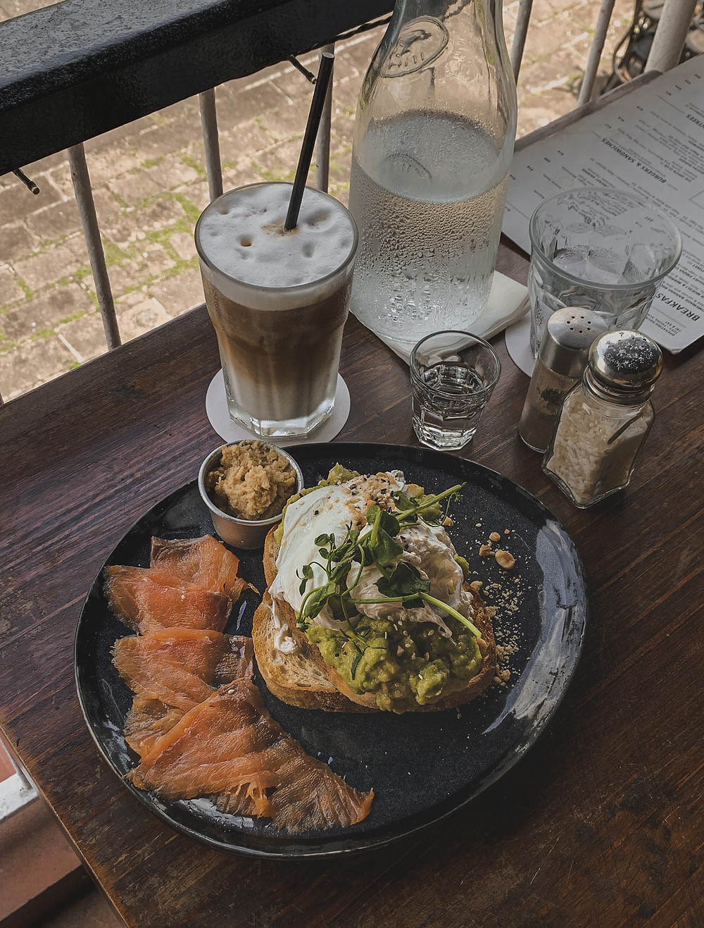 Poached eggs atop mashed avocado on toast served on a blue plate with a side of smoked salmon and iced latte