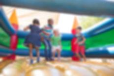 Kinder spielen auf Hüpfburg