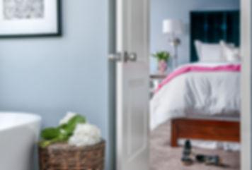 Elegant bedroom with blue upholstered headboard, interior desiger