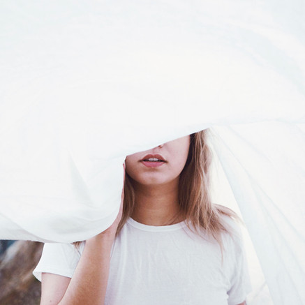 Woman Standing Behind White Sheet