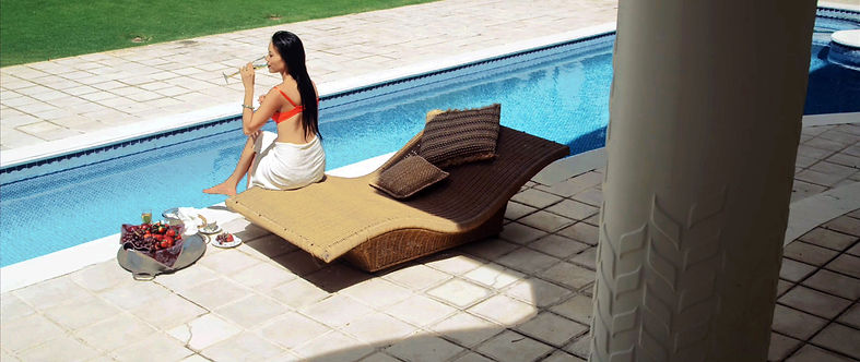 From the Vanderpoel film Redlove, the Art and Consequence of Illusion, showing a high angle view of a sunlit exterior with a swimmingpool and avant garde furniture and luxurious champaign and fruit enjoyed by a glamorous Asian beauty seated poolside