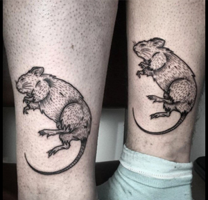 Two legs with identical tattoos of a dead mouse