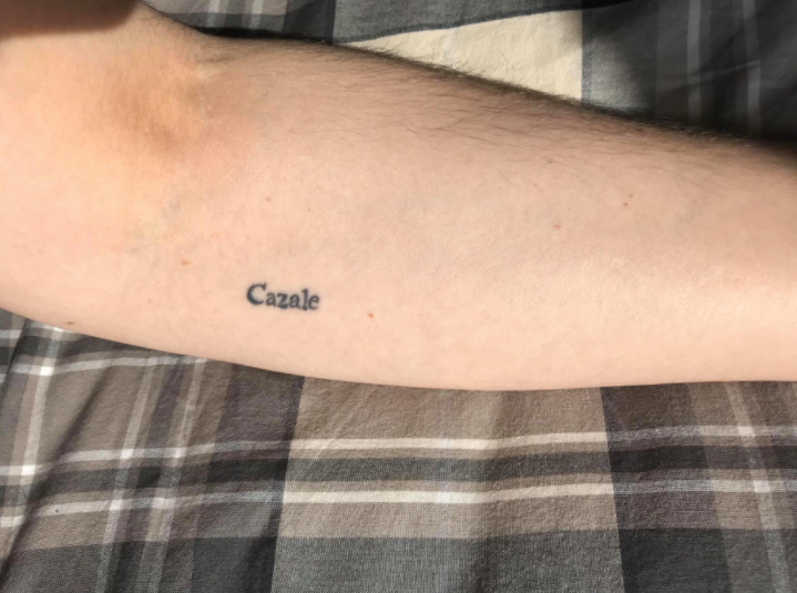 Tattoo on an arm saying the name cazale