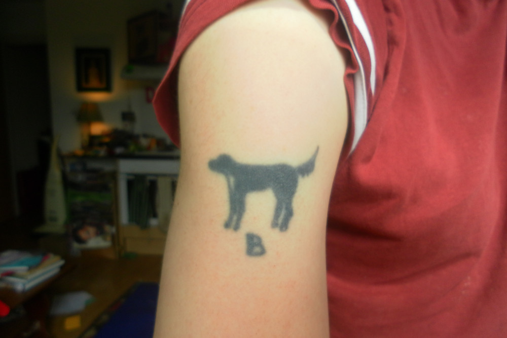 An upper arm with a tattoo of a black dog and the letter B underneath