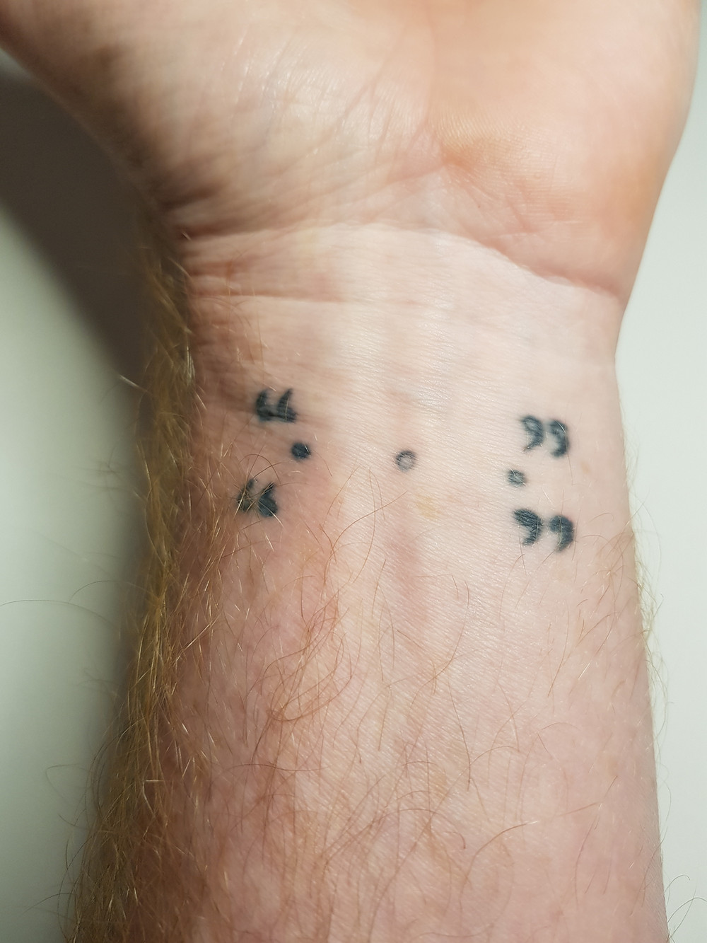 tattoo on a wrist of punctuation marks