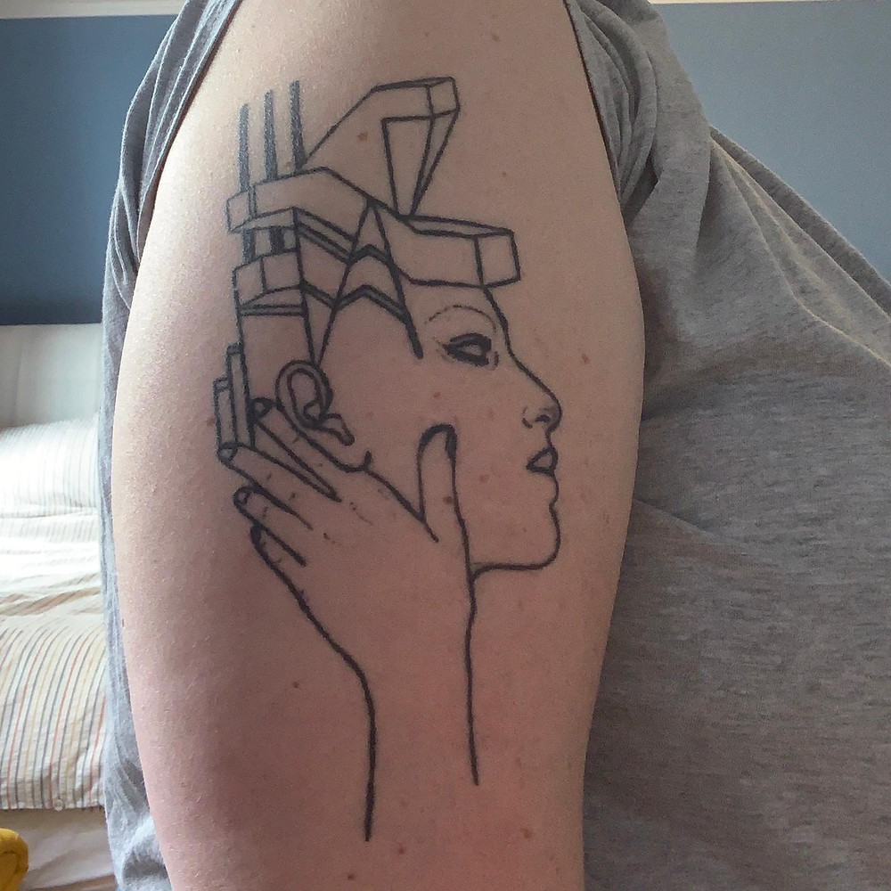 Tattoo on an arm of a face coming out of a building