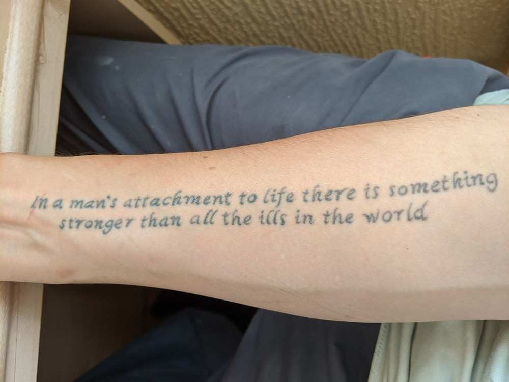 Tattooed quote on an arm. The quote says In a man's attachment to life there is something stronger that all the ills in the world.