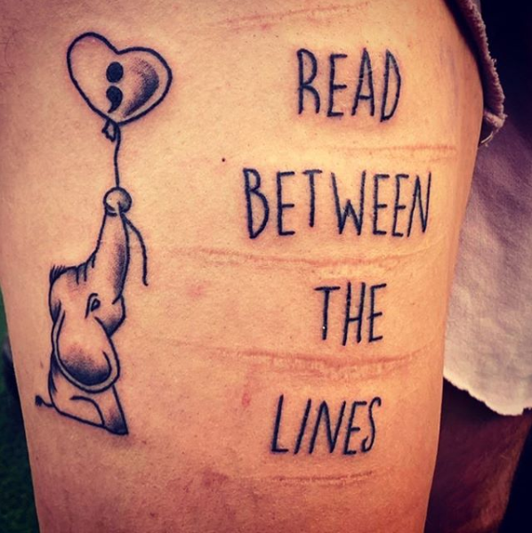 A tattoo saying Read Between The Lines. Also some self harming scars.