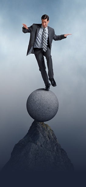 A man in a suit balancing on a stone ball on the tip of a mountain