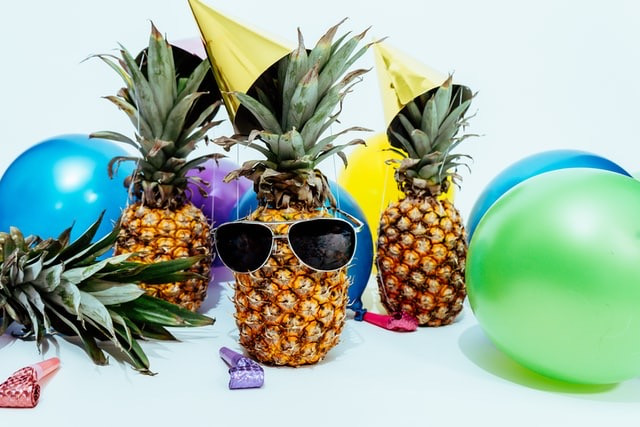 three pineapples dressed up with sunglasses and party hats, party balloons in green, blue and yellow, and party whistles