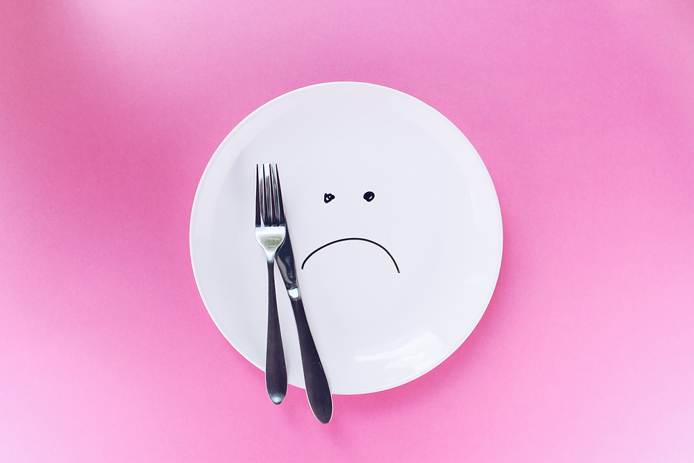 an empty white plate with a sad face drawn onto it and cutlery put on it, a pink background