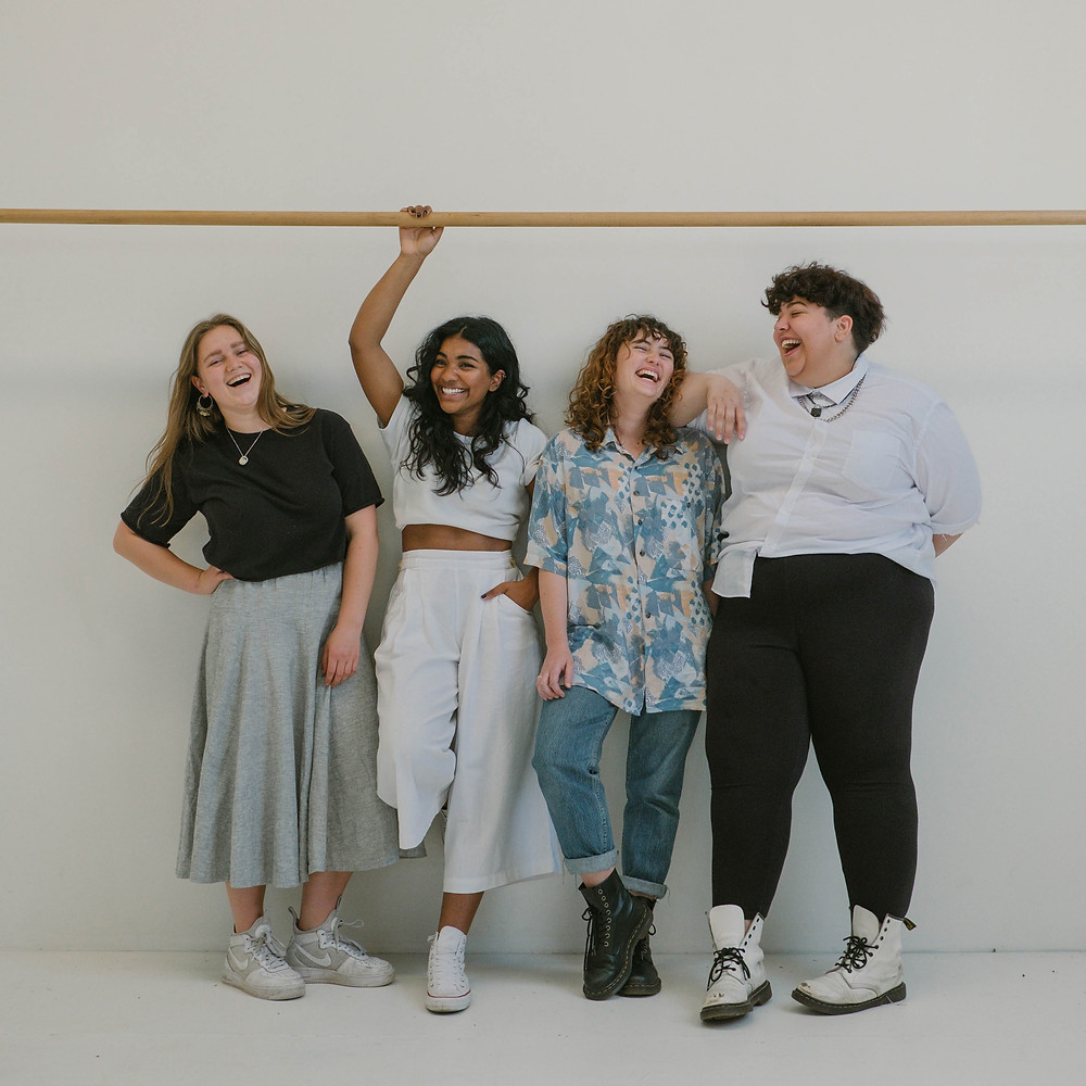 four females of different weights and sizes laughing, standing next to each other in front of a white backdrop with a wooden bar above them to which one of them holds on to