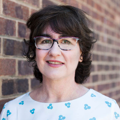 a picture of Celia, a woman with short dark hair, glasses and wearing a white shirt with blue spot pattern
