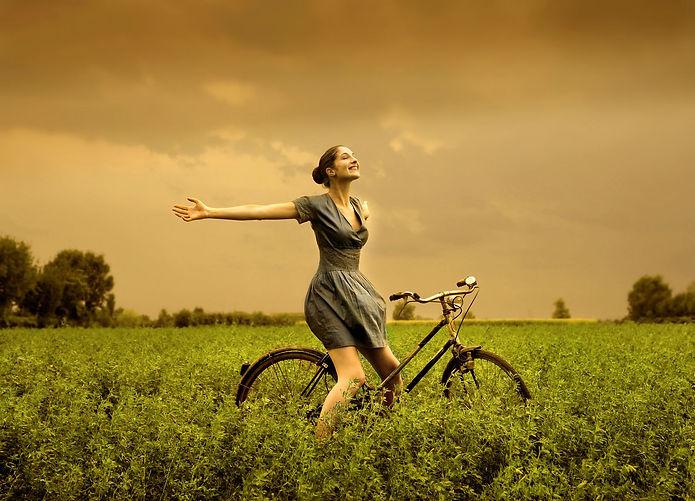 femme épanouie en pleine nature sur un vélo