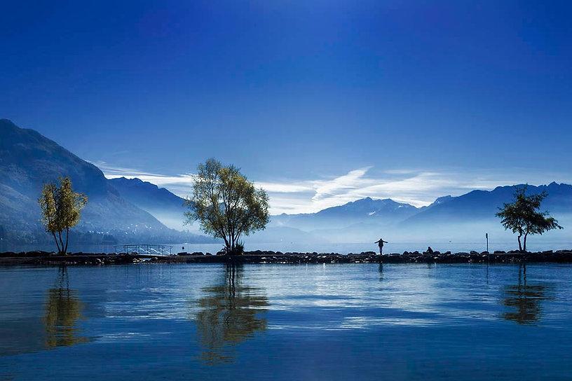 photographie d'un étang entouré de montagnes avec ciel bleu et brume