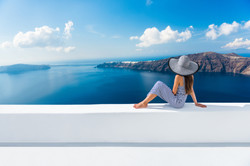 Europe Greece Santorini travel vacation. Woman looking at view on famous travel destination. Elegant