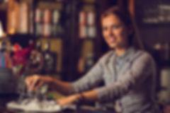 Smiling-female-bartender-cleaning-bar-co