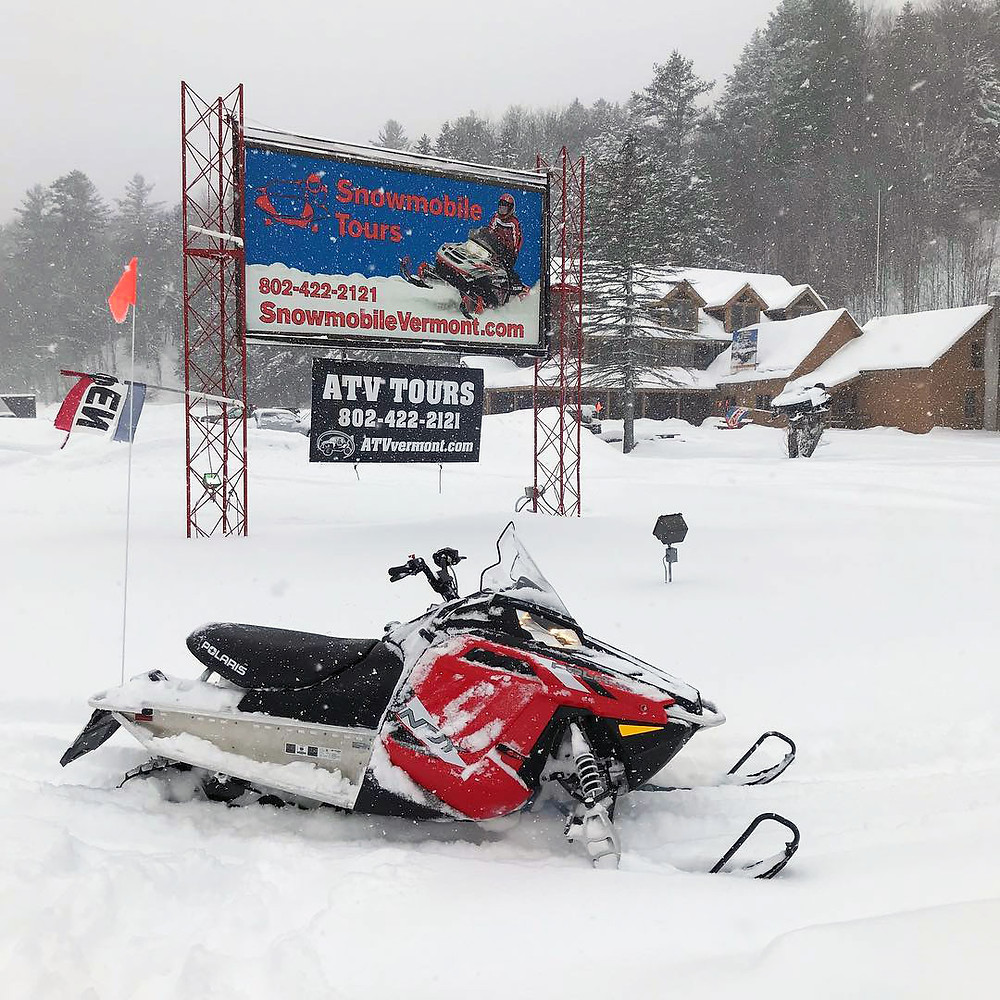 A snowmobile parked in front of Snowmobile Vermont's Killington-Okemo 1 hour tour location