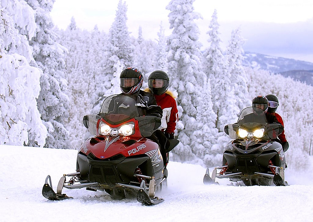 Two couples riding Snowmobile Vermont's Polaris snowmobiles with snow covered trees in the background