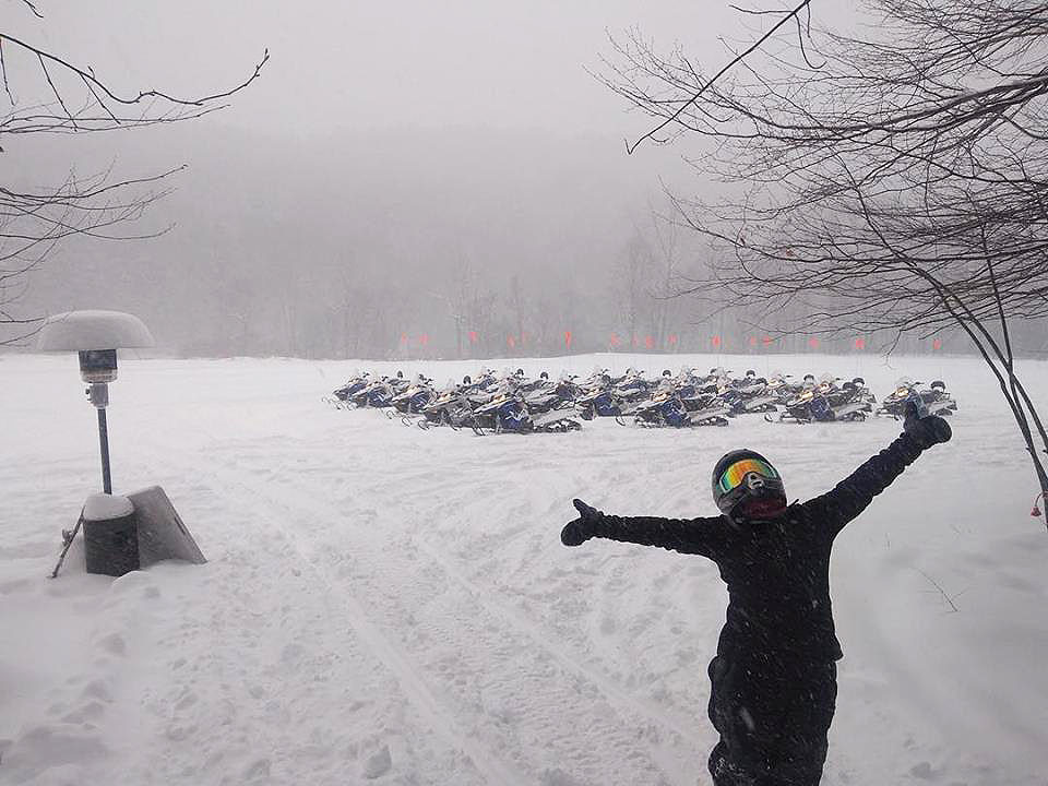 Happy snowmobiler standing in front of a group of snowmobiles in Vermont