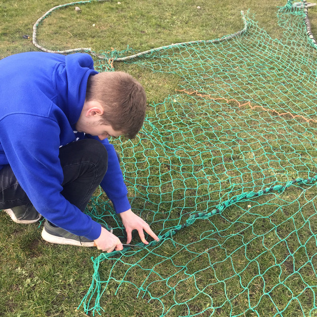 Participant reparing fishing net