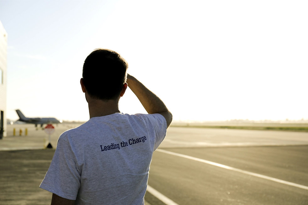 """A person looking out over an airport tarmac, text on his shirt says, """"Leading the Charge"""""""