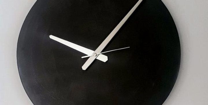 שעון קיר עגול מבטון חשוף וחלק בעיצוב תעשייתי מינימליסטי.