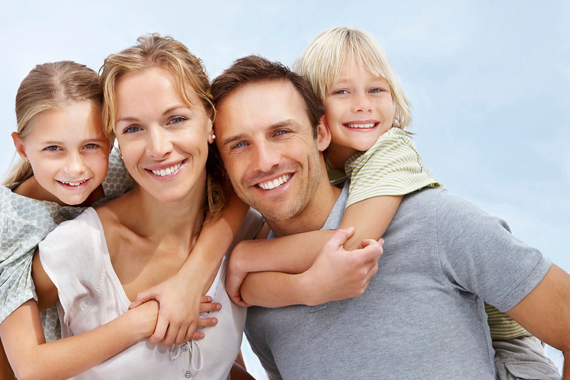 Portrait of happy mature parents carrying two kids on their back