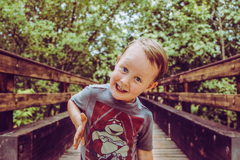 cure boy standing on a bridge and smiling and playing in the forest